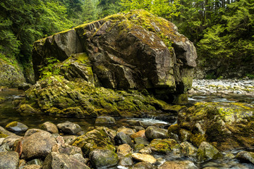 water running in the creek under a giant rock covered with mosses