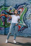attractive girl with tattoos holding skateboard over shoulder near wall with graffiti - 212698306