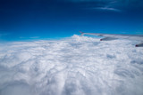 aerial view above the clouds with bluish sky and fluffy clouds