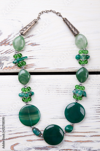 Beaded necklace with green polished stones. Close up expensive unusual jewellery. - 212708590