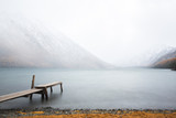 Old wooden pristine in the lake in foggy weather against the background of the mountains