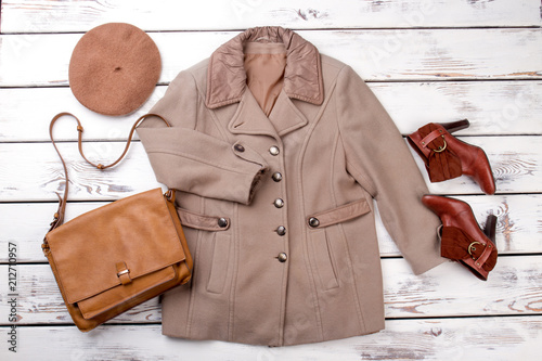 Aluminium Kameel Concept of brown winter clothing. Beige camel coat, handbag, hat and shoes. White desk wooden background.