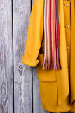 Close up yellow coat sleeve and scarf. Wooden desk surface background. - 212712950