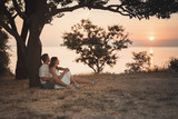 Beautiful scenery at dawn. A beautiful tree in the shape of a heart symbol. A loving couple sits hugging under a tree. - 212713709