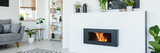 A stylish, lit bio fireplace in a living room interior of a modern, monochromatic apartment with white walls, wooden furniture and plants
