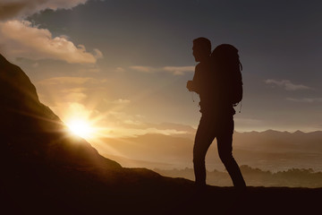 Silhouette of backpacker man hiking the mountain