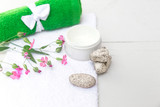 Spa beauty cosmetics on white marble table from above . Copy space. Flatlay. a jar of cream, leaves, flowers and a towel on a wooden background - 212720302