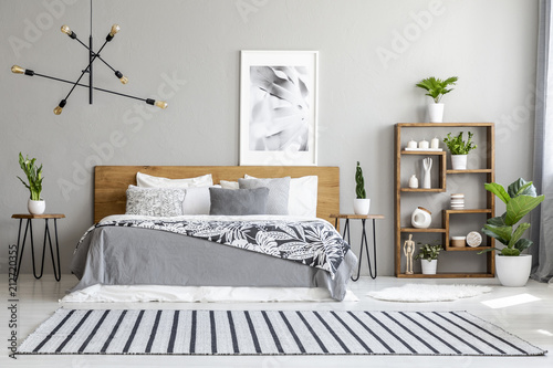 Striped carpet near bed with patterned blanket in bedroom interior with poster and plants. Real photo