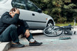 Worried biker holding his head and sitting on a pavement next to a car and bike crash