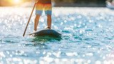Detail of young man standing on paddleboard. - 212721992