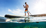 Young man on paddleboard, half under and half above water composition - 212722102