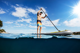 Young man on paddleboard, half under and half above water composition - 212722115