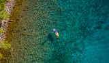 Aerial view of young man riding paddleboard - 212722345
