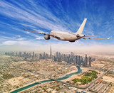 Commercial airplane flying above Dubai city - 212722374