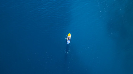 Aerial view of young man riding paddleboard