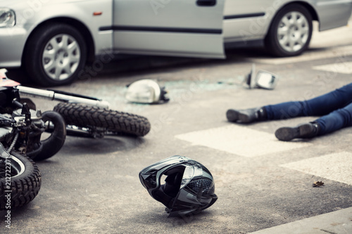 Helmet, motorbike and driver lying on a street where was the car accident - 212722371
