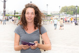 cheerful curly woman on tourist place with smartphone in Bordeaux center in France travel vacation