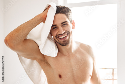 Naked man standing indoors at bathroom