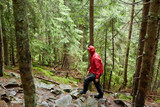 Man with raincoat hiking on a trail - 212742381