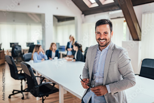 canvas print picture Portrait of successful entrepreneur, colleagues working in the background.