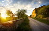 typical Tuscany countryside landscape; sunset over rolling hills and Tuscany village - 212744532