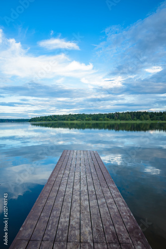 Plexiglas Pier view of the river from the shore with a beautiful sky and clouds
