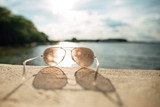 Sun glasses on beach near the sea. Yellow sunglasses on the background of sea wave on the shore of a tropical island. Depth of field blur