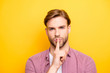 Leinwandbild Motiv Close up portrait of confident pensive dreamy handsome sexy guy with stylish modern hairdo holding forefinger near mouth asking to be quiet isolated on bright yellow background copy-space