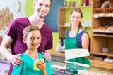 Father and son buying cheese at organic supermarket counter - 212759350