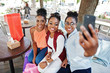 Three casual african american girls with colored shopping bags walking outdoor. Stylish black womans shopping and making selfie on phone.
