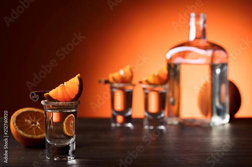 Szkła tequila z pomarańczowymi i cynamonowymi kijami na drewnianym stole.