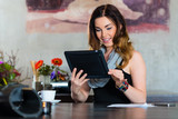 Young woman in a cafe or restaurant, she using her tablet computer for emails and video chat - 212763374