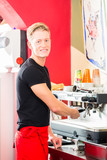 Barista using coffee machine or unit and preparing espresso or cappuccino in coffeehouse or shop - 212763516