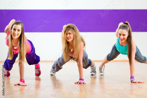 Fototapeta Young women dancing modern group choreography in dance school