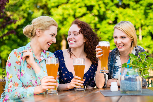 Leinwanddruck Bild Happy friends toasting with beer in garden pub