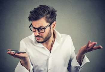 Man with smartphone in misunderstanding