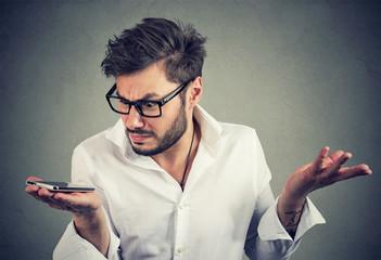 Man with smartphone in misunderstanding © pathdoc