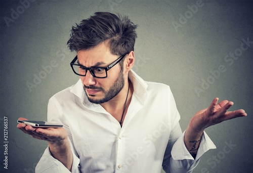 Man with smartphone in misunderstanding - 212766537