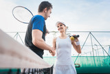 Man and woman shaking hands after match of tennis