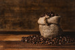 Leinwanddruck Bild - bunch of fresh roasted coffee beans with burlap sack on a wooden table. agriculture and drink concept