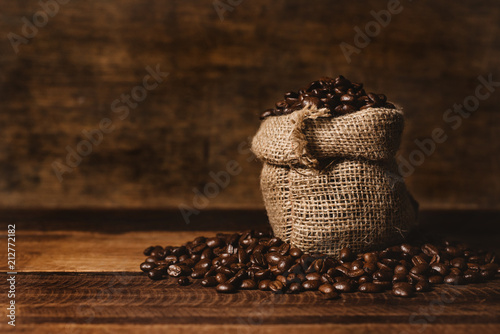 Leinwanddruck Bild bunch of fresh roasted coffee beans with burlap sack on a wooden table. agriculture and drink concept
