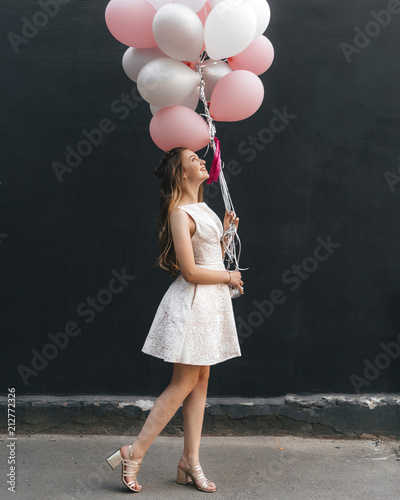 beautiful young girl in a dress with balloons on a black wall background