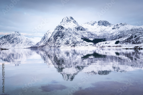 Fotobehang Blauwe hemel Mountain ridge and reflection at the water. Beautiful natural landscape in the Norway