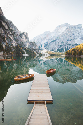 Traditional rowing boats at Lago di Braies at sunrise in fall, South Tyrol, Italy