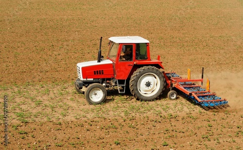 Aluminium Trekker Red and white tractor with a hoe tiller cultivator machine as trailer on a land field with little plants