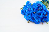 Blue cornflowers bouquet on white wooden background. Copy space