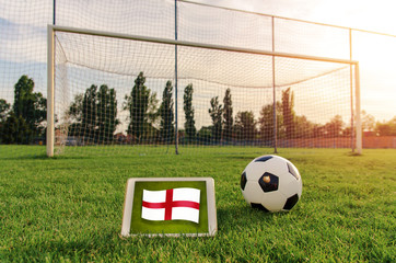 Soccer ball in front of empty goal and flag of England on digital tablet on the grass ;  Bright future