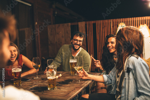 Group of friends drink beer on the terrace during summer night © djile