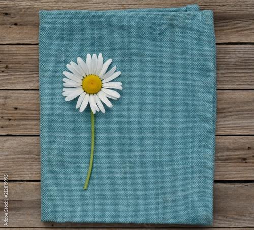Daisy on blue napkin and wood background - 212819995