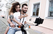 Happy couple on scooter making selfie on smartphone outdoor